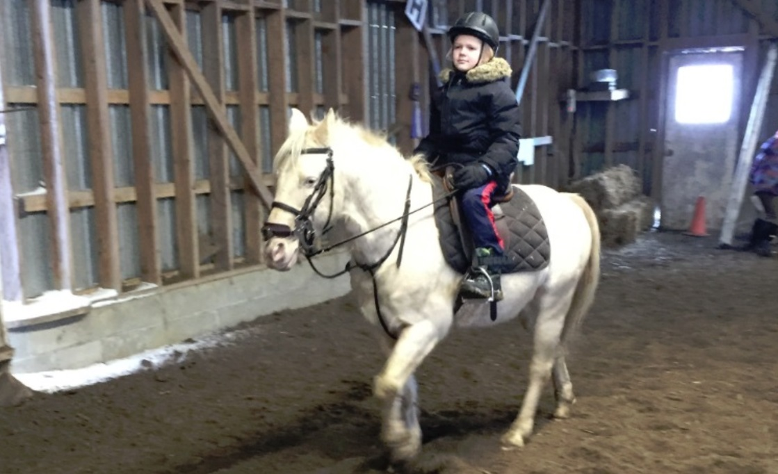 HeadsUp Dad child learns equitation on horseback in riding lessons